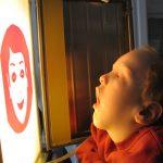 Frühförderung für Kinder mit Mehrfachbehinderung – Kind betrachtet Gesichterschema auf Lichtkasten