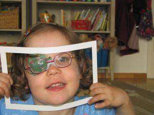 Frühförderung für Kinder mit Sehschädigung – Kind mit Occlusionspflaster auf Auge schaut durch gebastelten Papier-Bilderrahmen