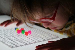 Frühförderung für Kinder mit cerebral bedingter Sehbeeinträchtigung – Kind betrachtet Perlen auf Steckbrett ganz nah