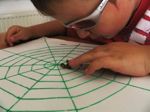 Frühförderung für blinde Kinder – Kind ertastet tote Biene im aufgemalten, tastbaren Spinnennetz